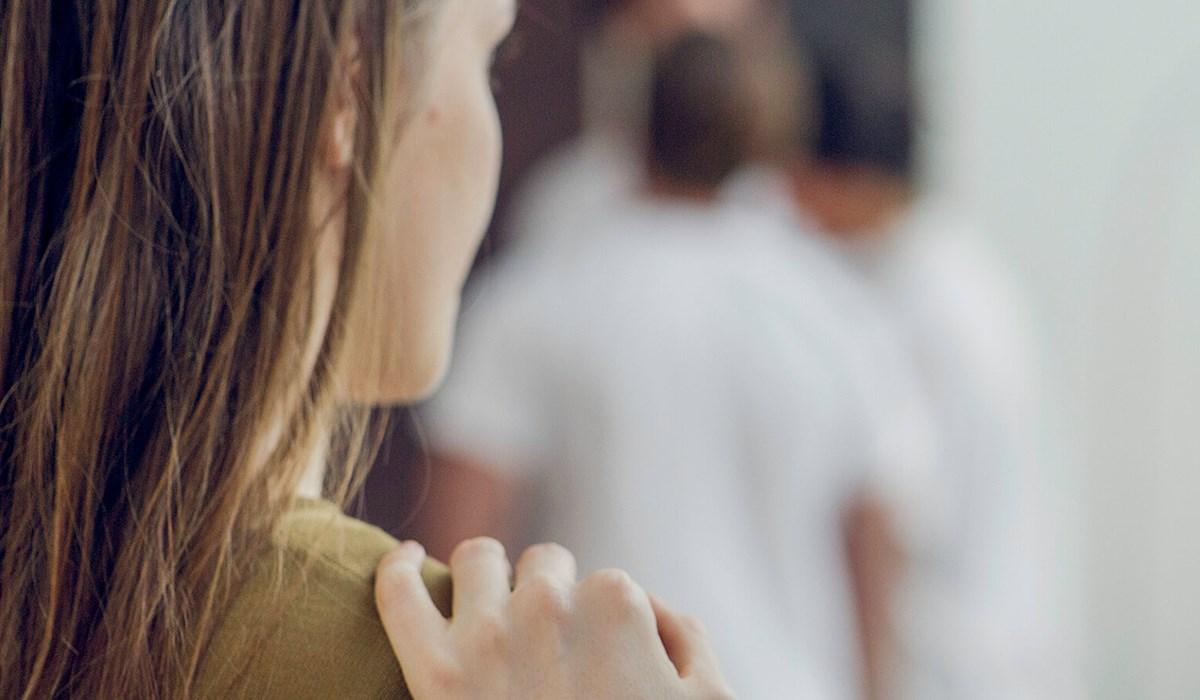 En person med en anden persons hånd på sin skulder
